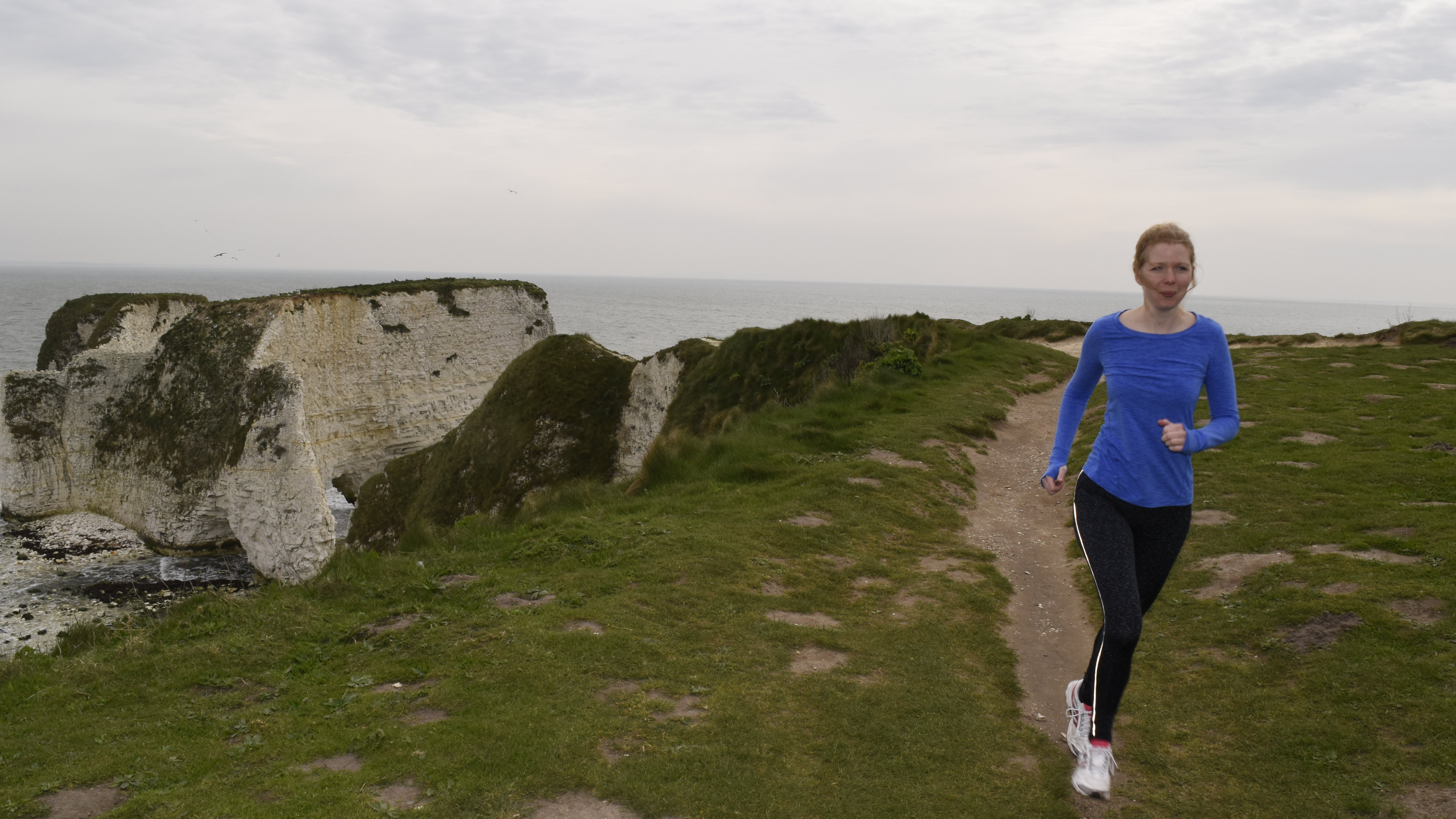 A runner passing Old Harry Rocks at Studland Bay