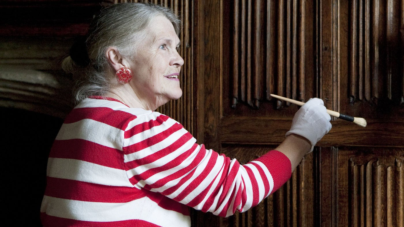 A lady, with a special brush, cleaning the grooves in the linen-fold panelling