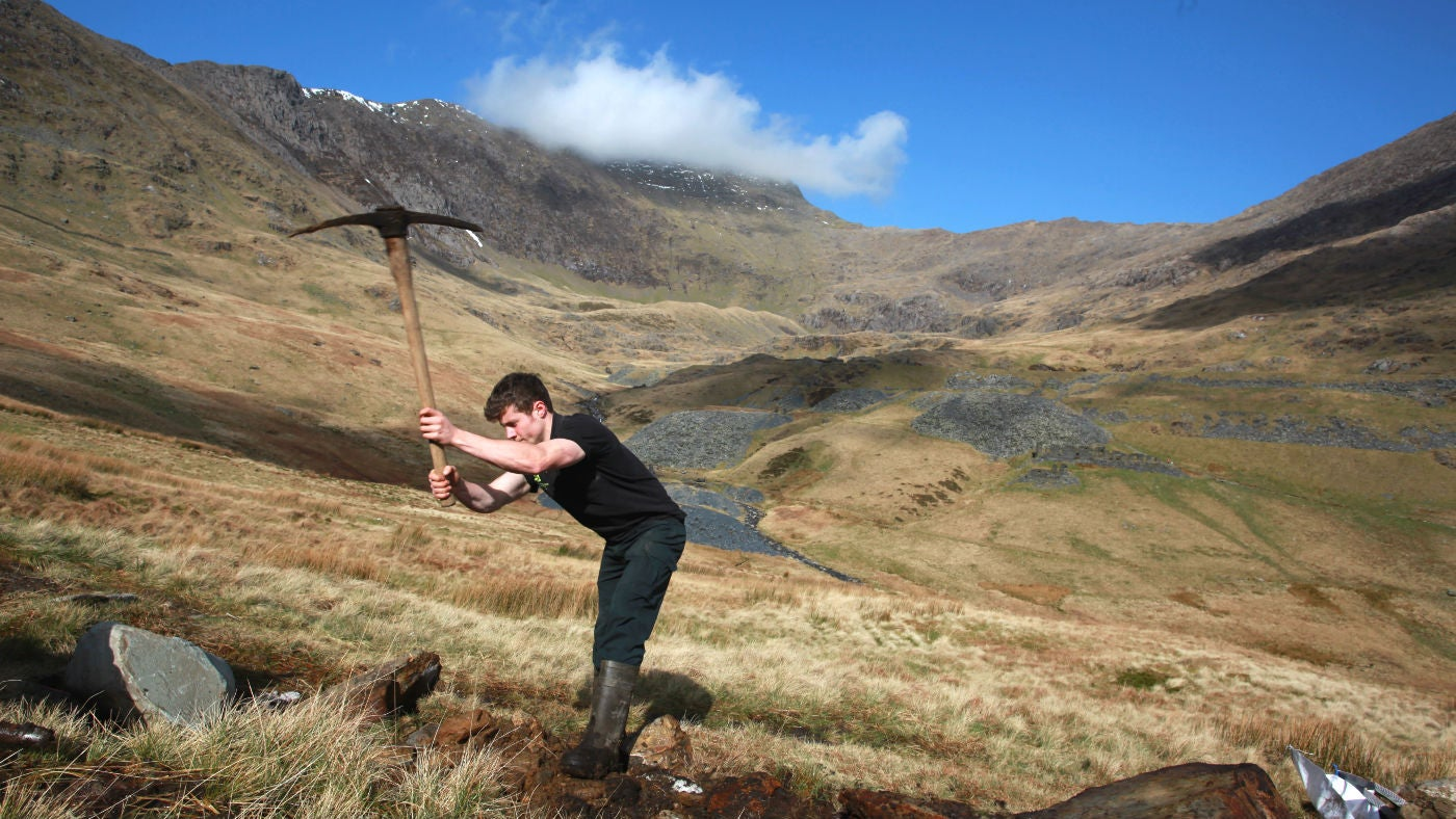 Ranger with a pick-axe working on footpath repairs, South Ridge of Snowdon in the background.