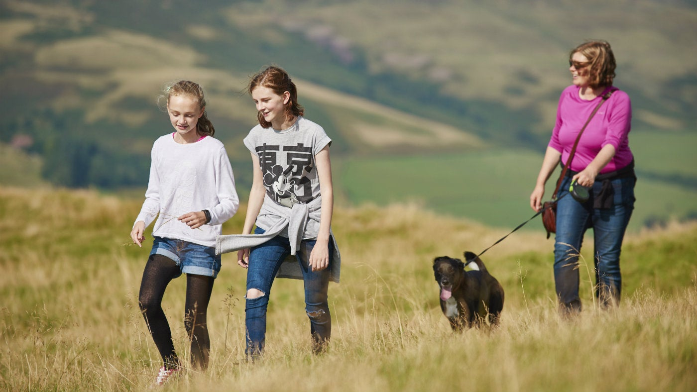two girls walking in grass and woman behind with dog on lead