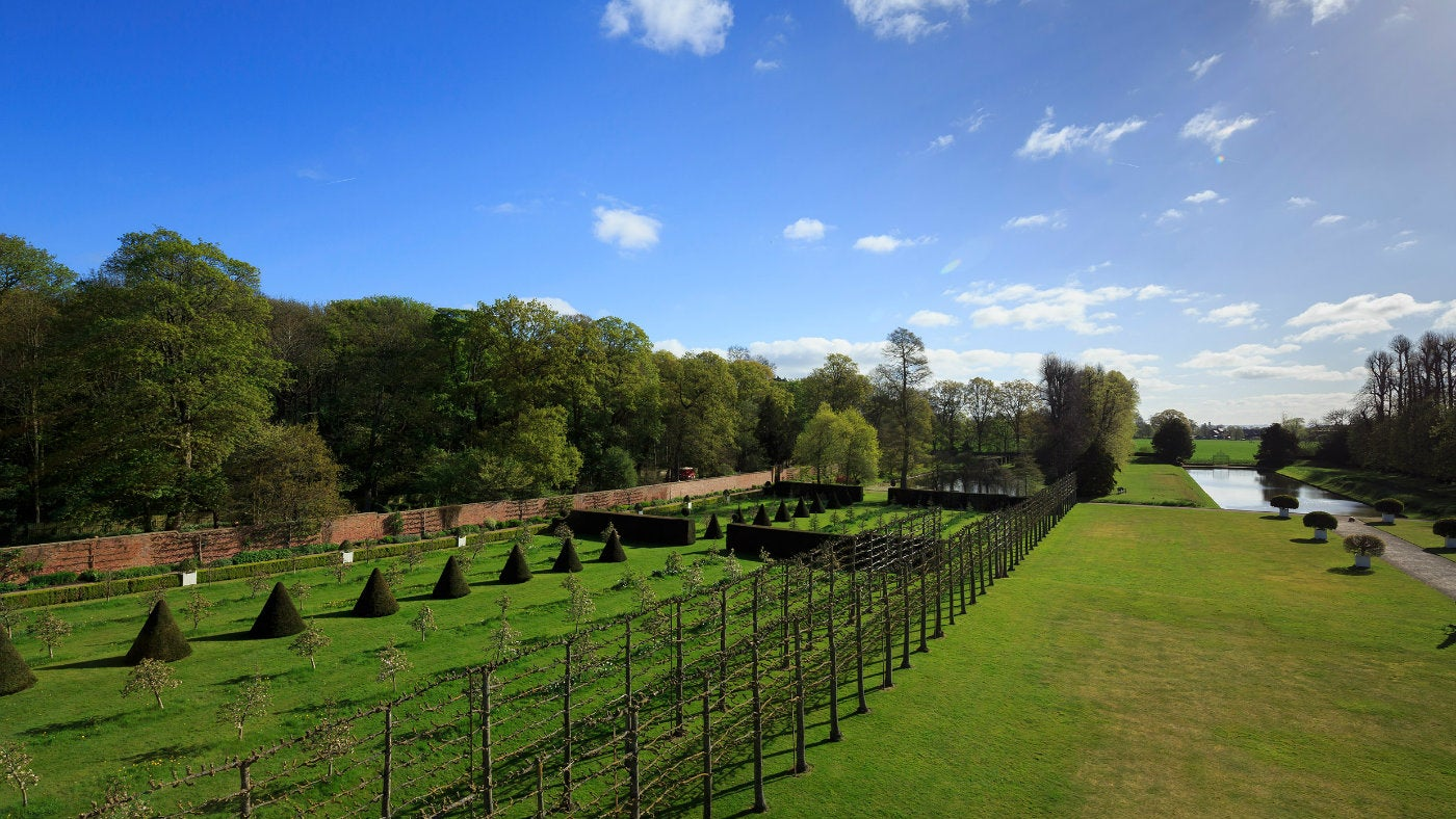 Elevated garden views of grand lawns, topiary and pleached limes facing east at Erddig