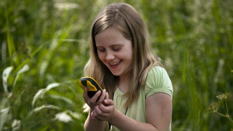 A girl enjoys geocaching in the great outdoors
