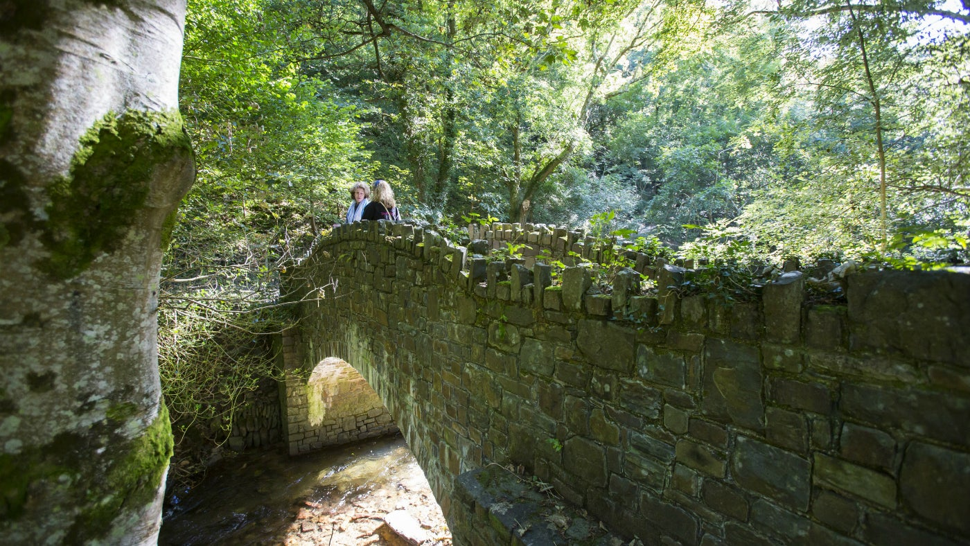 Visitors stand on a stone bridge at Heddon Valley