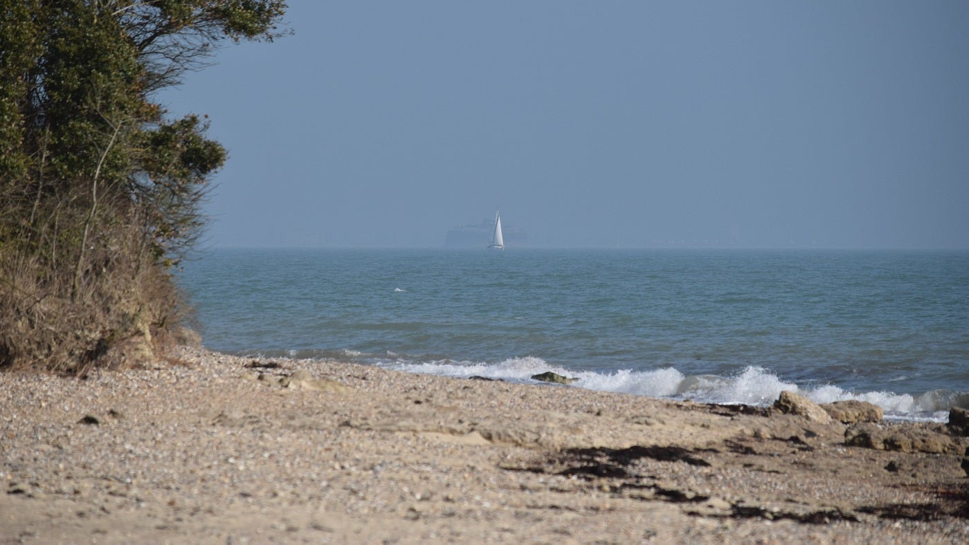 The sandy beach at Nodes Point with a boat in the distance