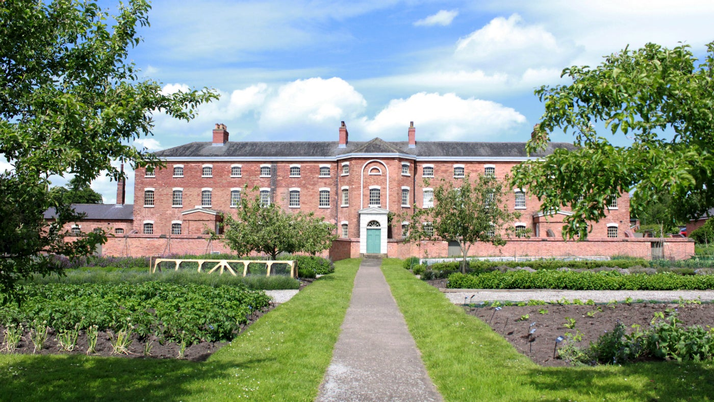front of The Workhouse in the summer with gardens and trees