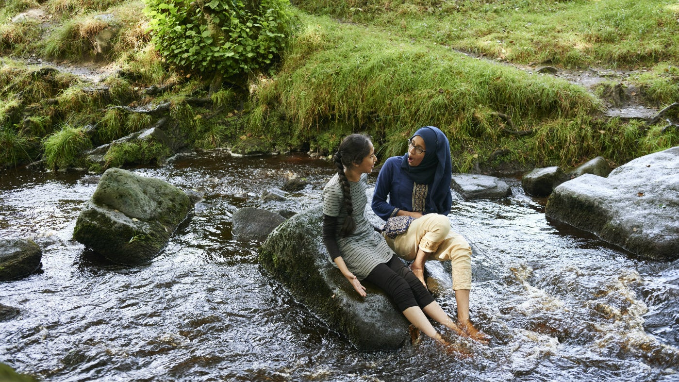 two girls sitting on rock in stream