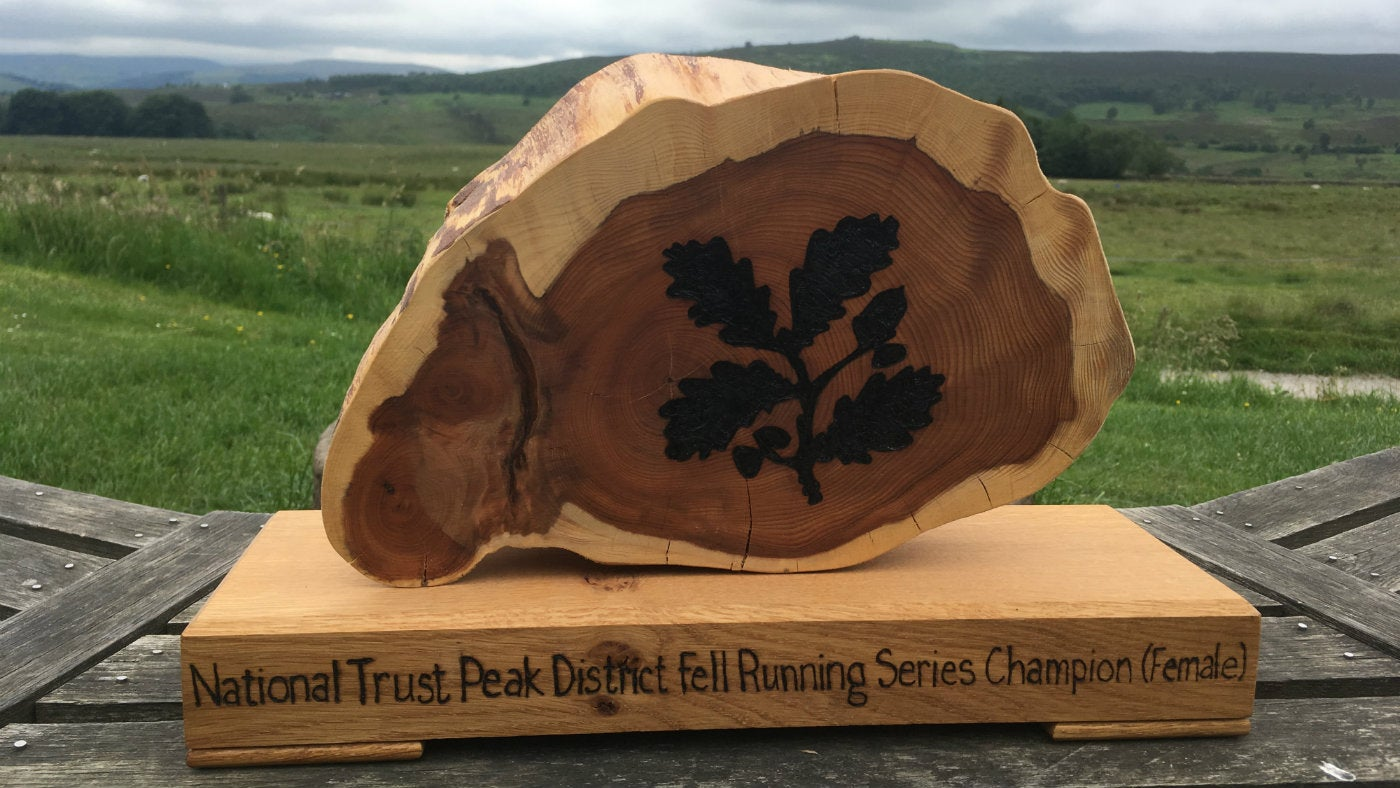 wooden fell running trophy on table with landscape view behind