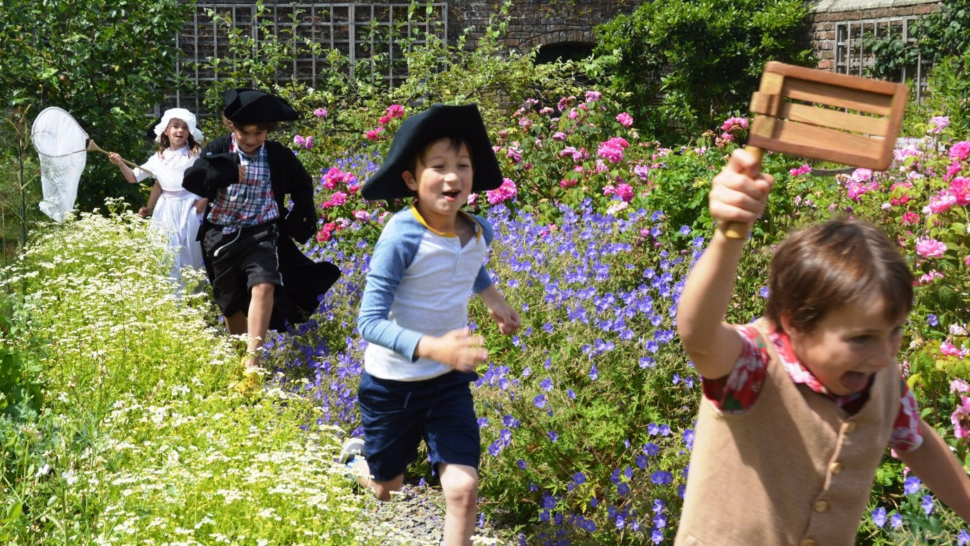 A group of children in dressing up clothes run through a garden