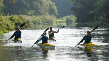 A group kayaking on the lake at Tredegar House