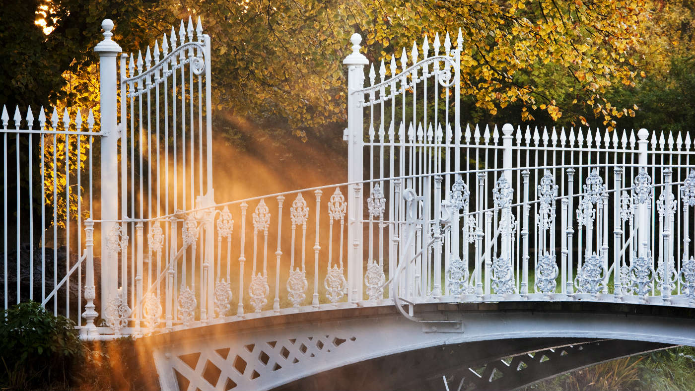 A warm glow surrounds the cast iron bridge over the River Wandle in Morden Hall Park, London.