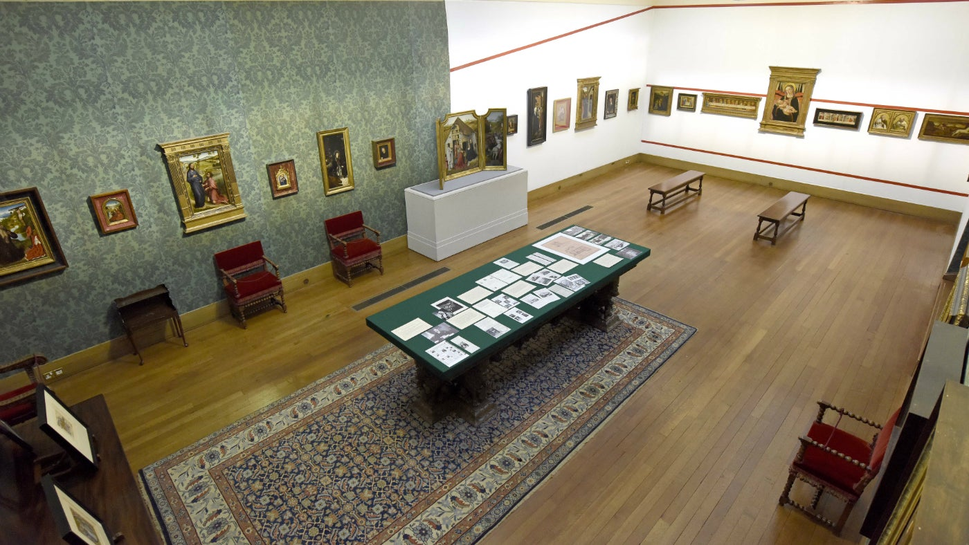 View of a painitngs gallery showing green or white wall covering on which the paintings are hung