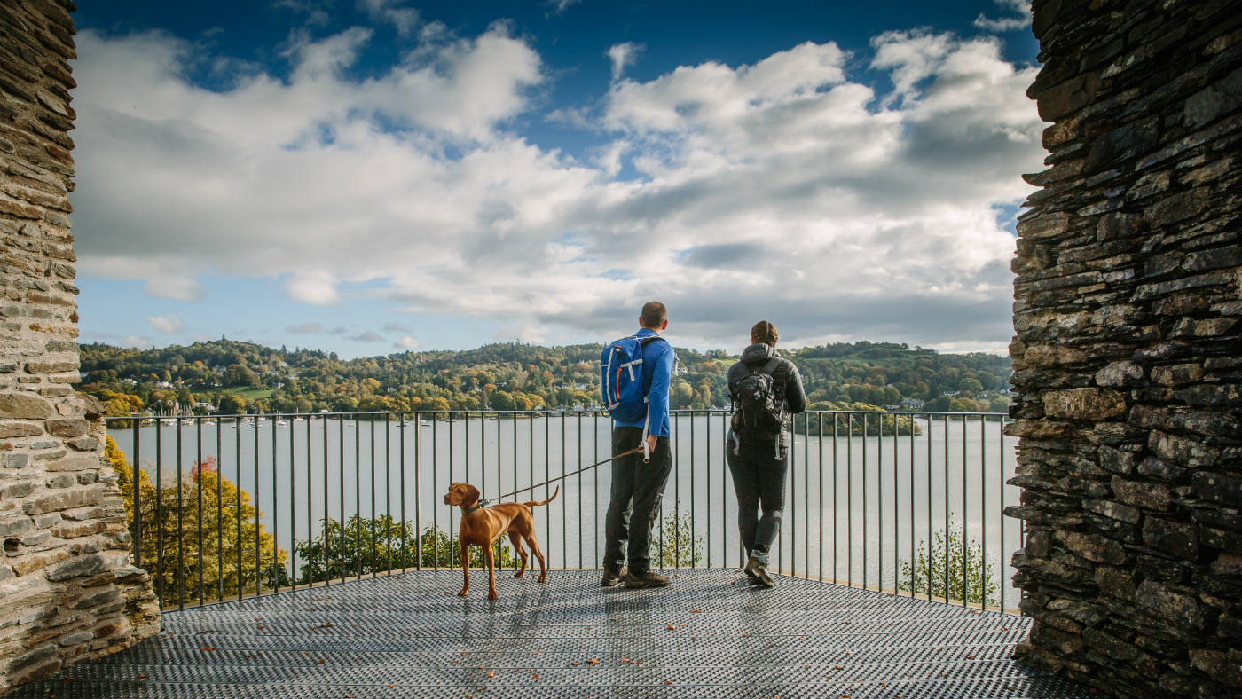 Couple with dog enjoy the autumnal view from the platform at Claife Viewing Station