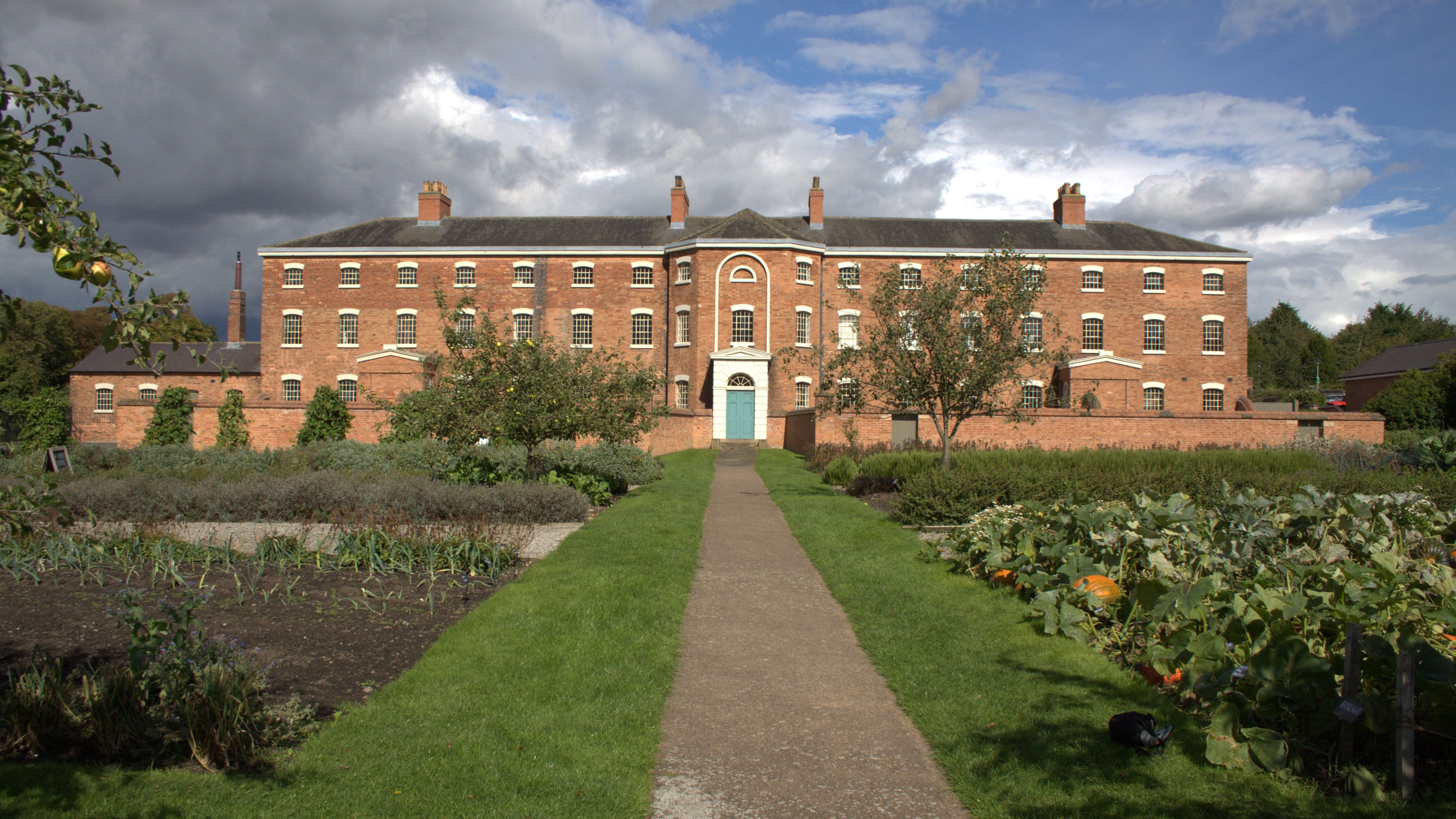 View of the front of The Workhouse in autumn showing the garden with pumpkins and apples