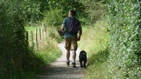 A man walking along a footpath with his black cocker spaniel