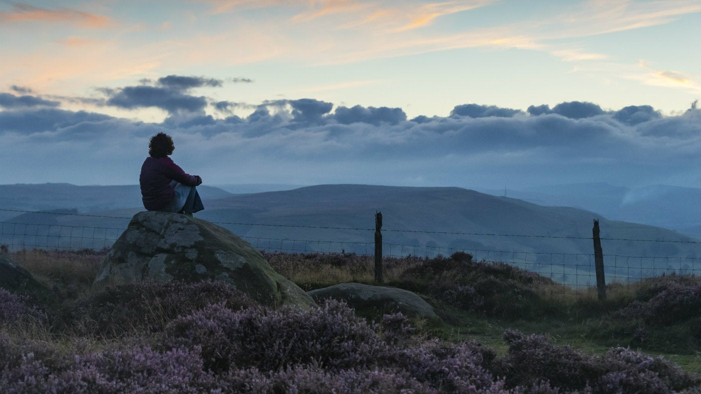 Visitor enjoying the sunset from a rock at Longshaw, Burbage