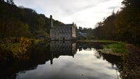 A stone mill and its reflection into a still pond