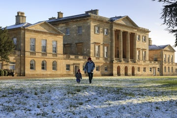 Family walking in front of Basildon Park house with a ligt snow covering the ground