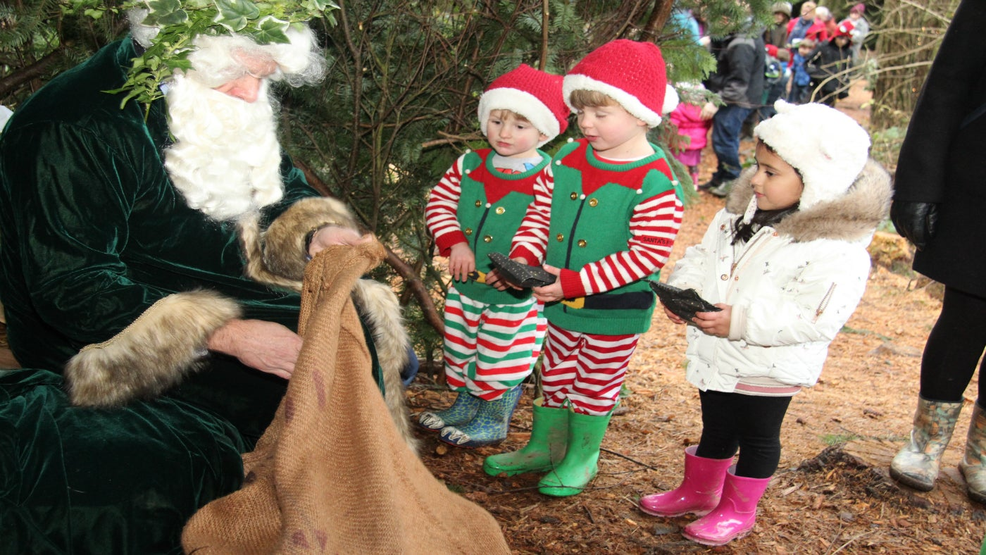 Father Christmas in green robes giving out presents to a group of children dressed as elves