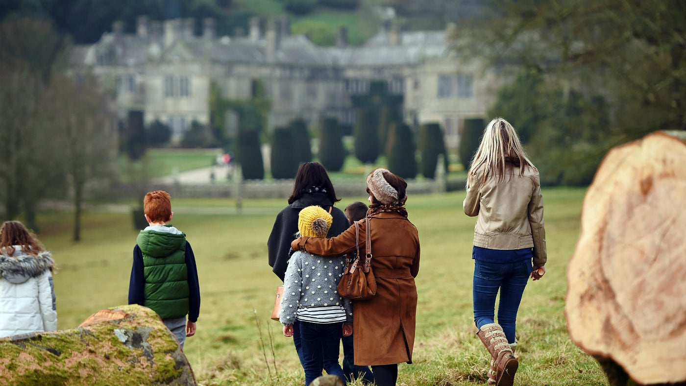 A family walking through the parkland towards Lanhydrock House in Cornwall