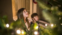 Children looking up at Christmas tree lights