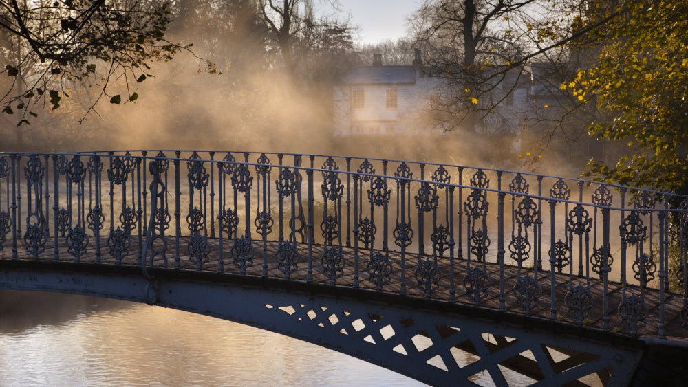 Mist rising over the River Wandle with white bridge in foreground