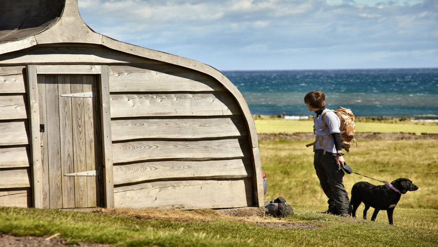 A dog walker near the boat sheds at Lindisfarne Castle