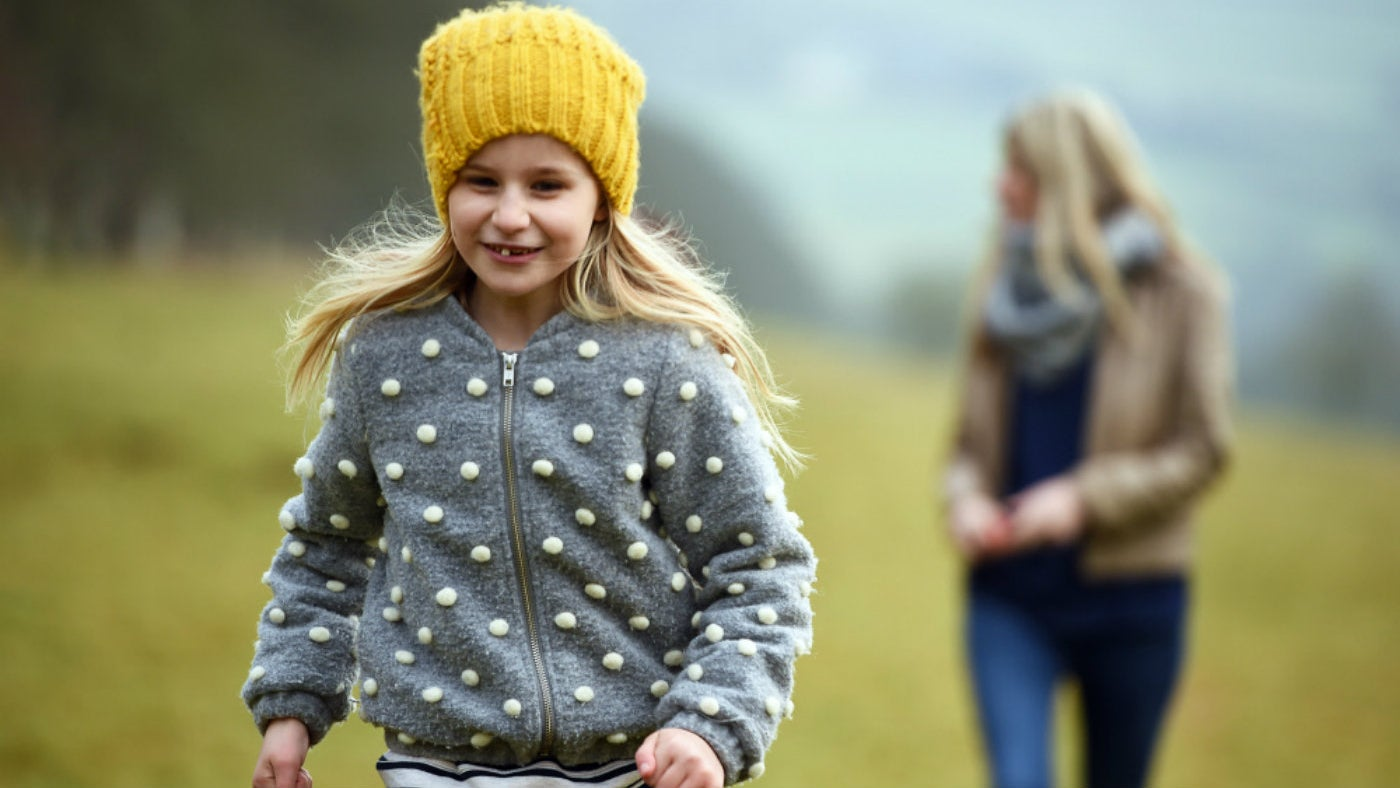 A girl in a yellow hat enjoys a winter walk at Hindhead Commons and the Devil's Punch Bowl