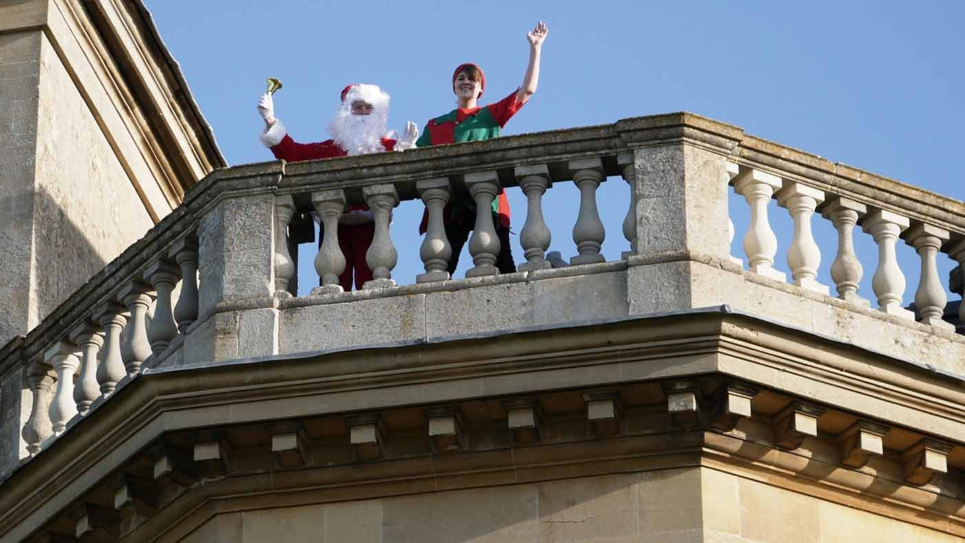 Father Christmas with his Elf on the balcony at Croome Court