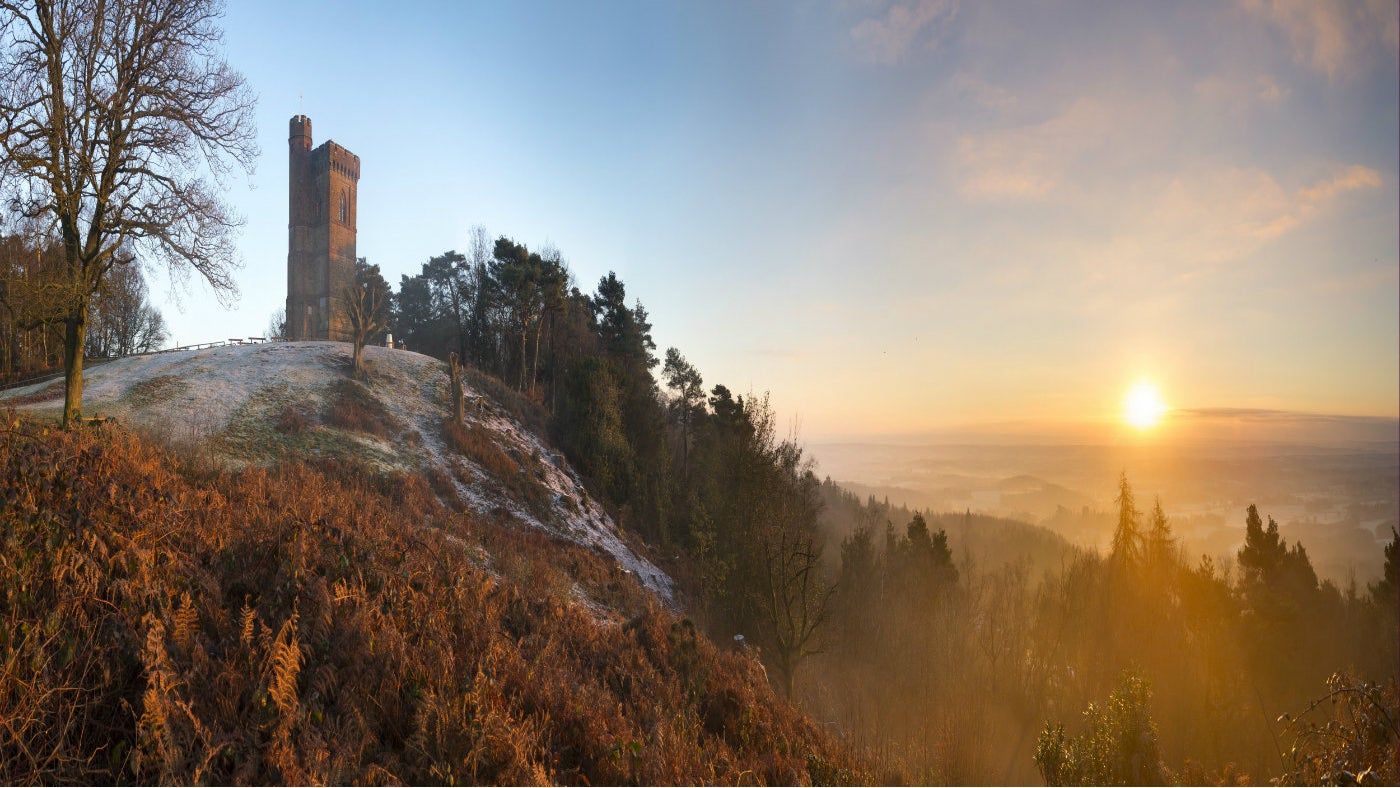 The sun rises over Leith Hill and Leith Hill Tower on a winters' morning