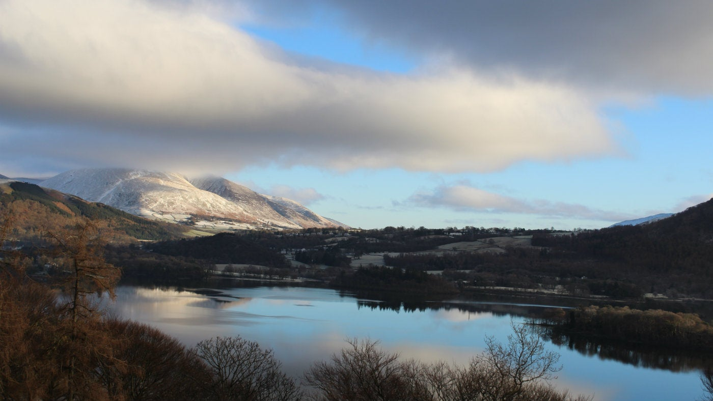 Low cloud shrouds a snowy Blencathra, reflected in a still Derwent Water.