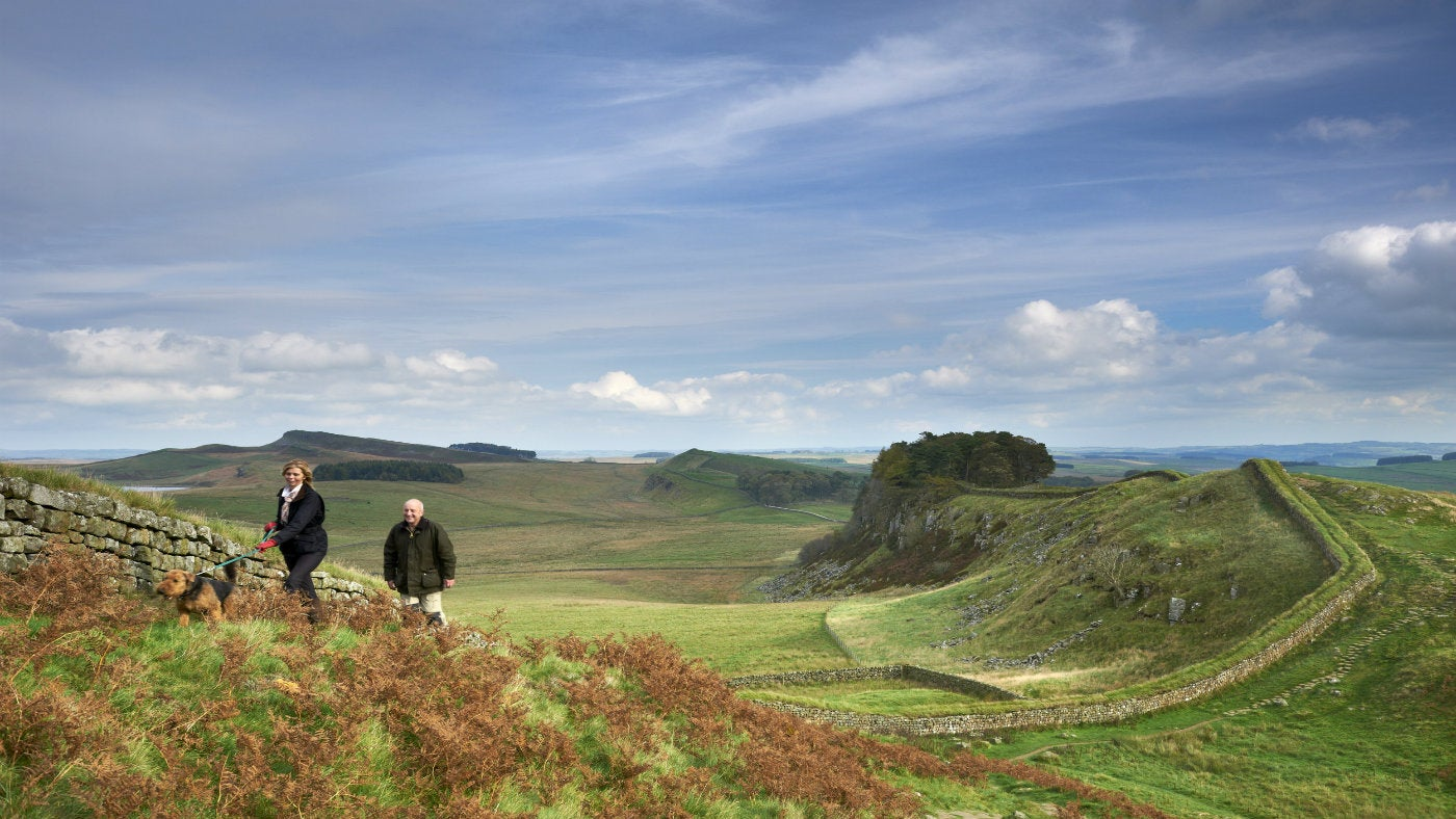 A small group of people walk alongside Hadrian's Wall