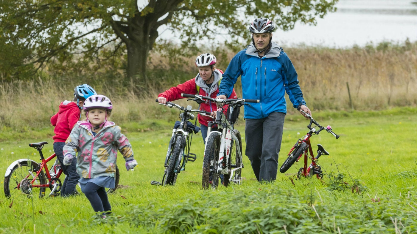 A family enjoy cycling by Blickling's lake