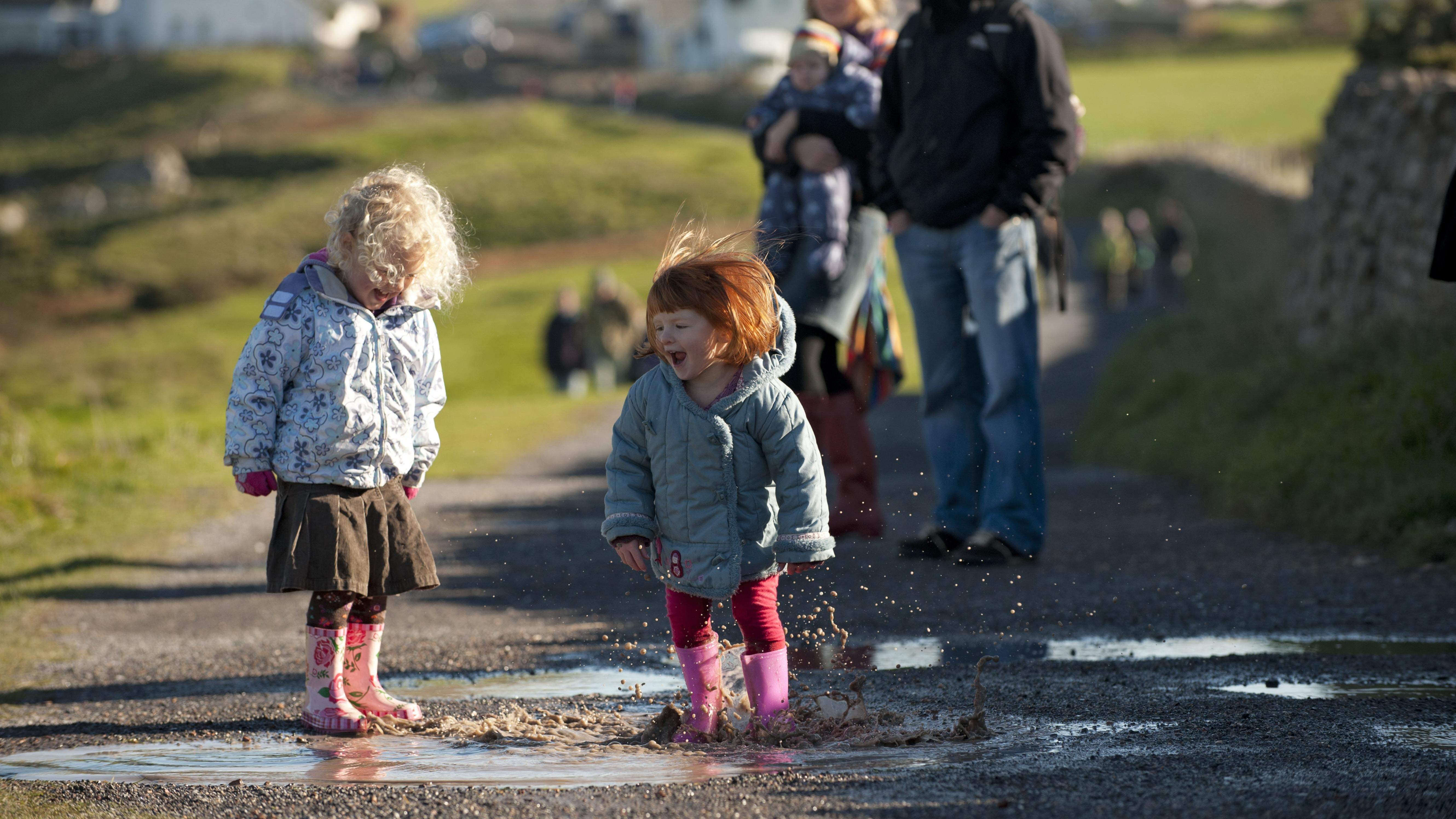 Two little girls splashing in puddle with parents in background