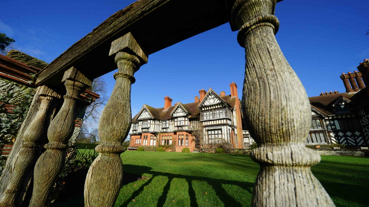 Looking through the balustrades on the south terrace lawn towards Wightwick Manor in the sun