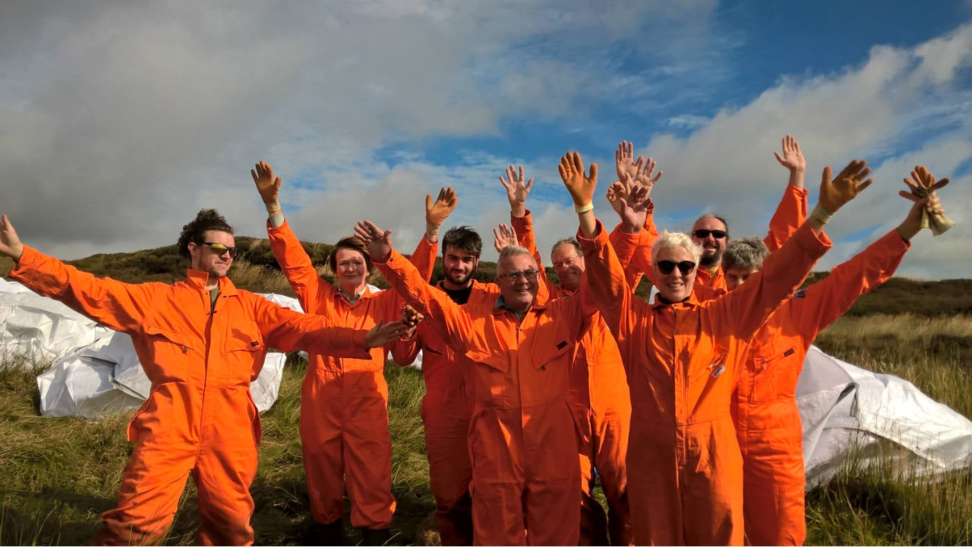 Marsden Moor Volunteers in orange bolier suits, arms in the air.