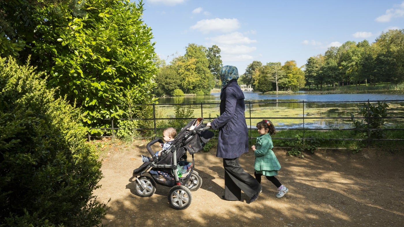 A mum pushes a child in a buggy with a little girl walking next to her on a path at Stowe. Beyond the path is a view of a lake and large Grecian style Palladian Bridge