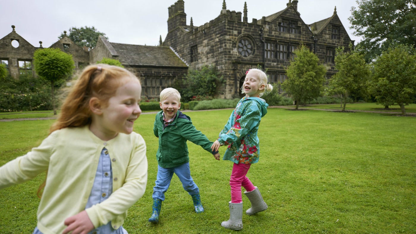 Three children running and laughing on the lawn