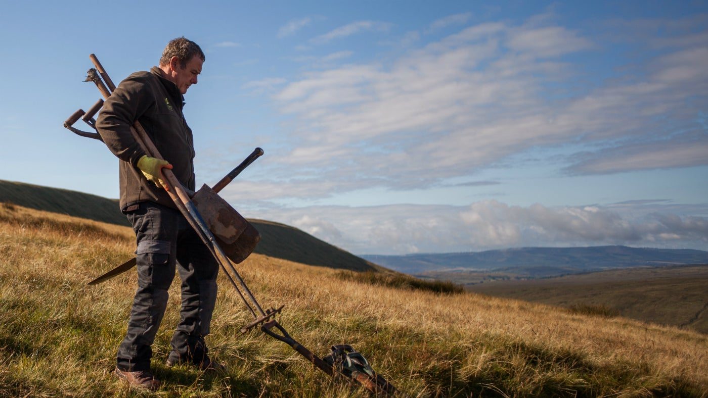 Lead ranger for the Brecon Beacons National Trust carrying tools in preparation for footpath repair work