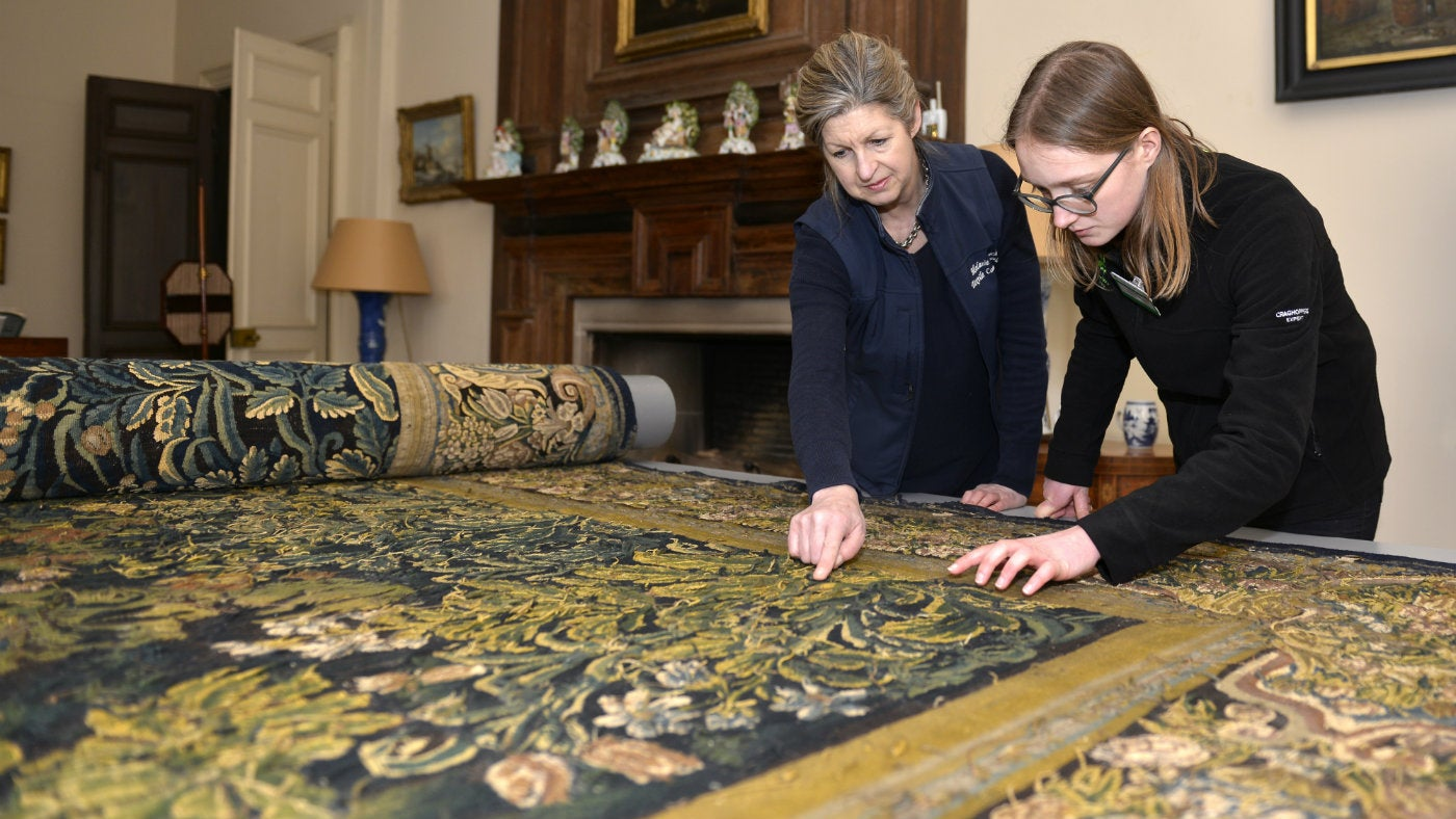 Two women bent over a rolled up tapestry