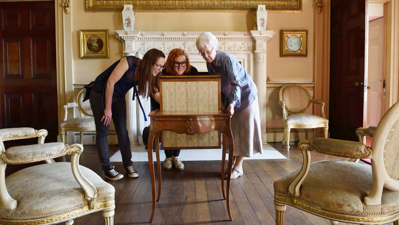 Three women looking at furniture in a historic room