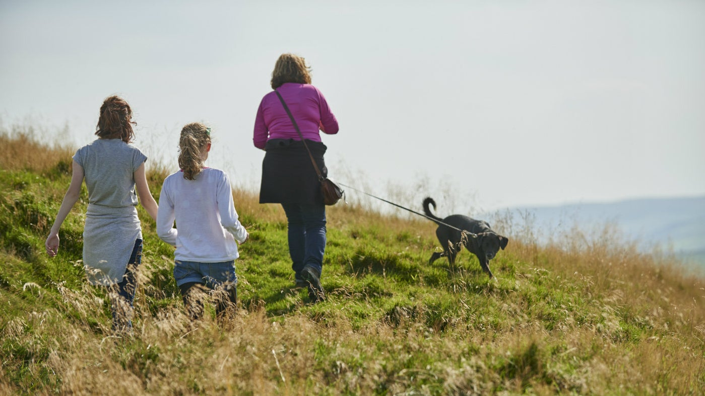 family with dog enjoying a walk