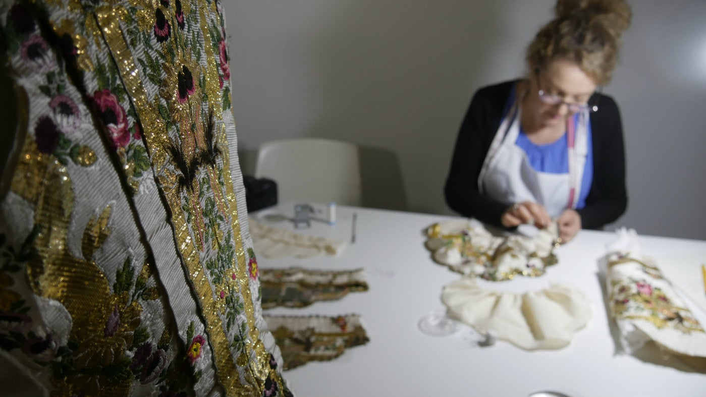 Conservator stitching into the silk of the Ann Bangham dress
