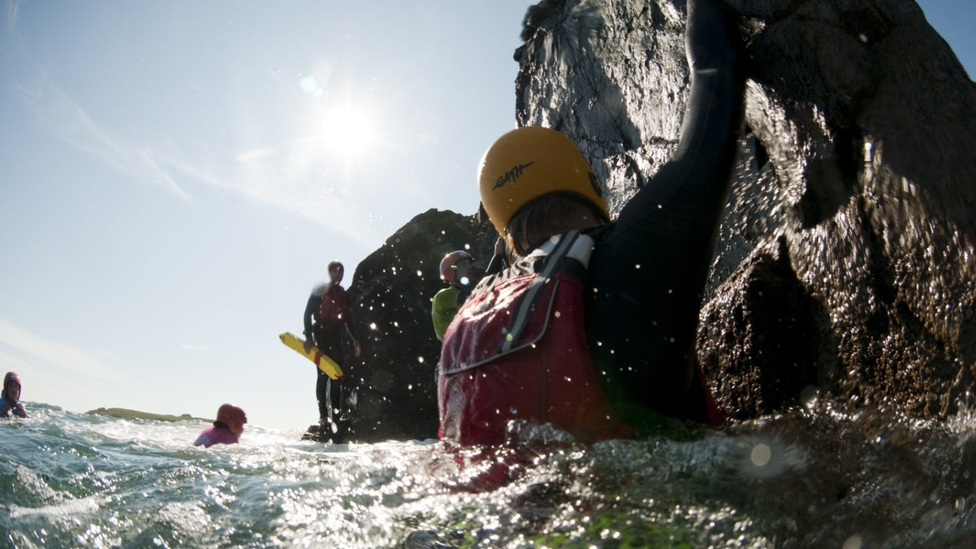 Visitors in wet suits swim off a rocky shore as they enjoy a coasteering event