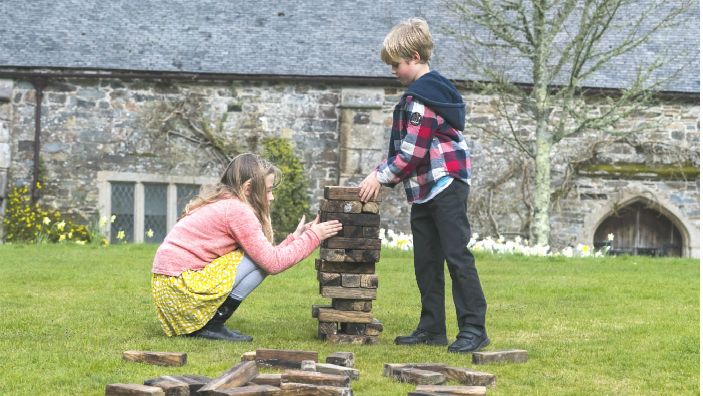 Children playing giant jenga in front of Cotehele house