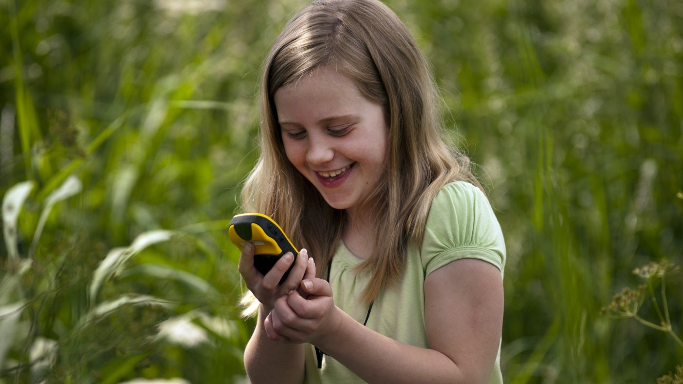 A smiling girl holds a GPS unit on a geocaching event