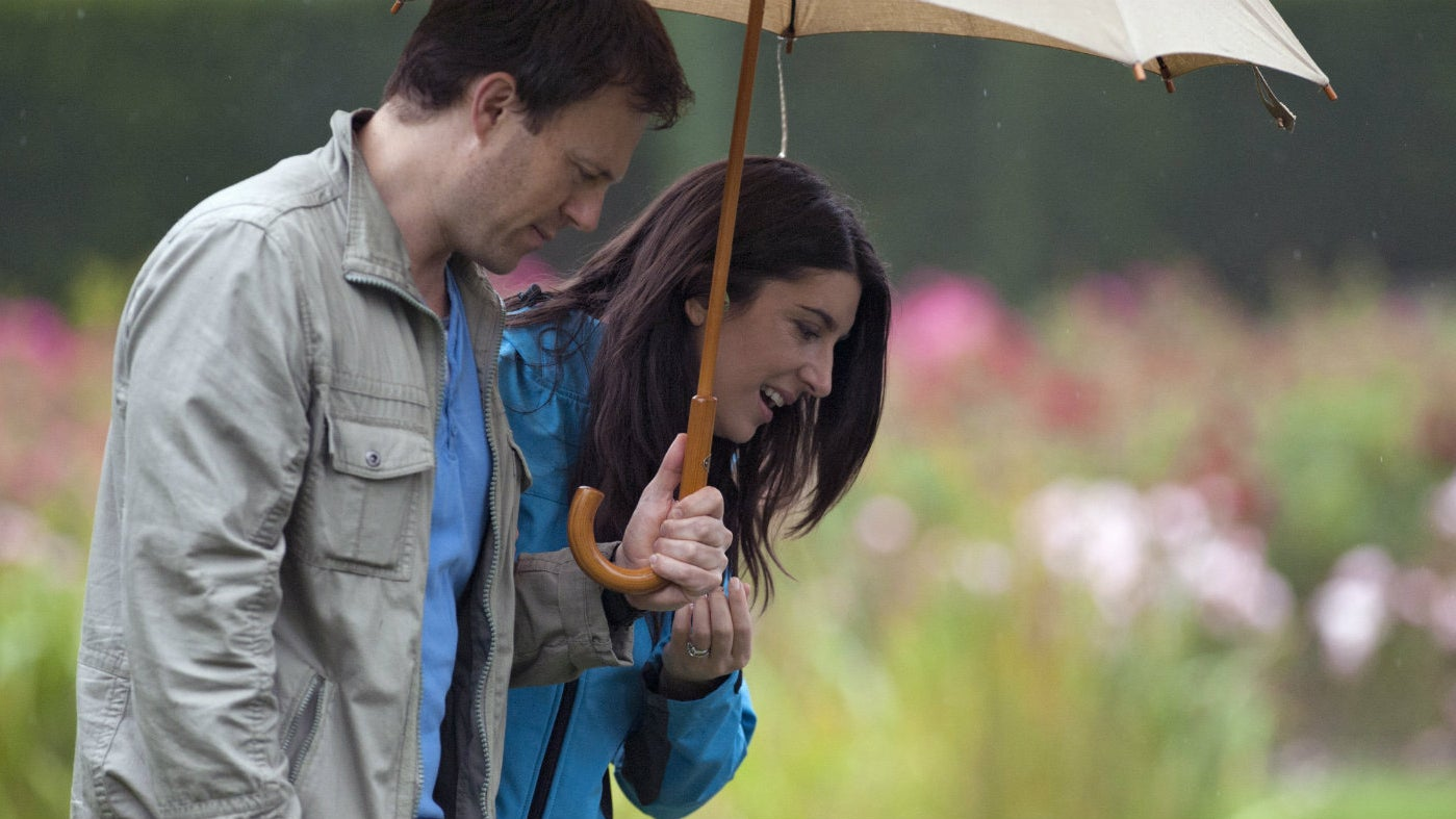 A couple stand looking at the gardens with an umbrella covering both of them