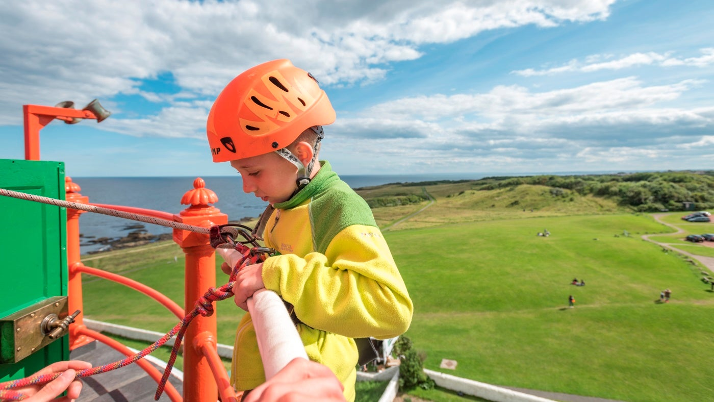 A young child at the top of Souter Lighthouse prepares to abseil down the tower