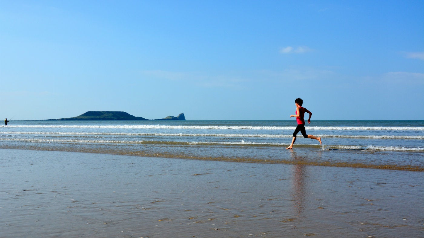 Running across the beach at Rhossili, Gower