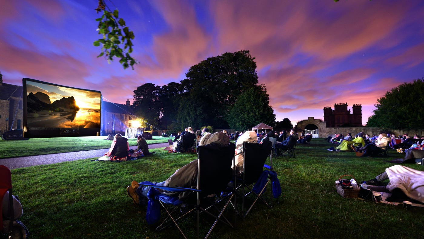 Visitors watching a cinema on a screen in the garden at Hardwick