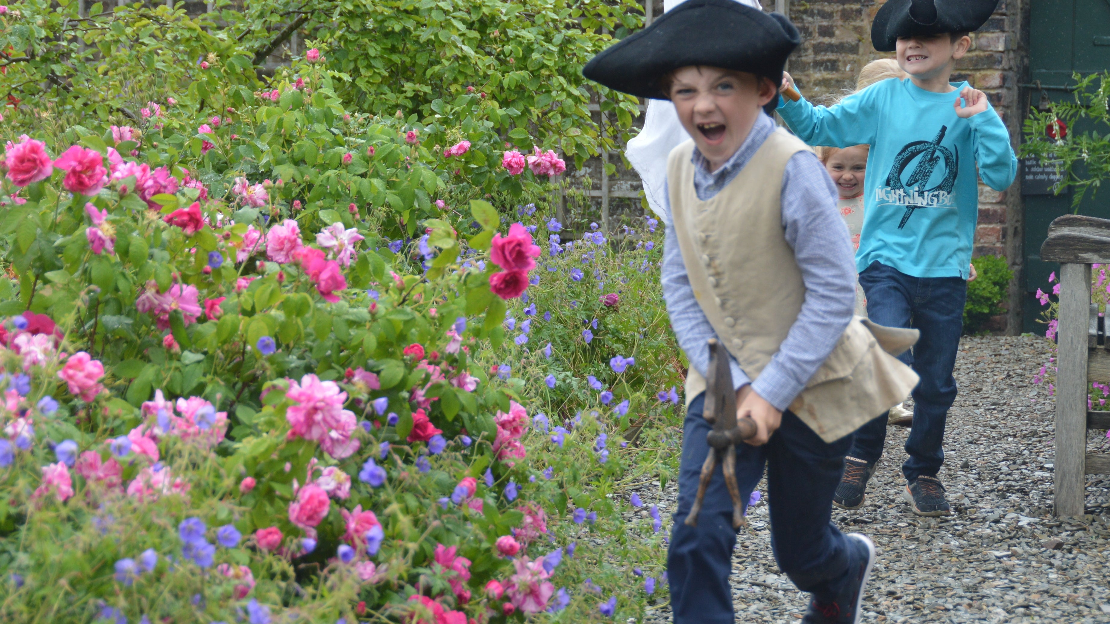 Children wearing tricorn hats running about in a garden